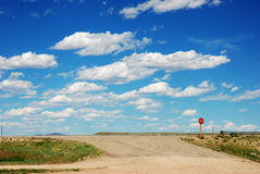 Approach to highway. Dirt road approach to highway with stop sign Stock Photo