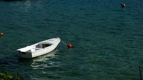 Approached a white wooden boat with orange buoy in the water. In the Bay of Montenegro stock video