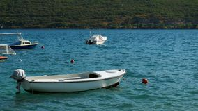 Approached a white wooden boat with orange buoy in the water. In the Bay of Montenegro stock footage