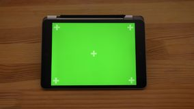 Approaching close-up horizontal view of tablet with green screen on wooden desk background. Approaching close-up horizontal view of tablet with green screen on stock footage