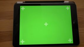 Approaching close-up shot of horizontal tablet with green screen on wooden desk background. Approaching close-up shot of horizontal tablet with green screen on stock video footage
