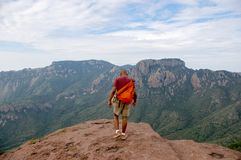 Approaching the Edge. Young black man approaching edge of a cliff Stock Photo