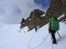 Approaching a mounitain pass. Roped team of mountaineers approaching a mountain pass Stock Images