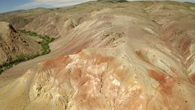 Approaching one of the most beautiful rainbow mountains in Altai, Aerial view on grass-covered sandstone hills in front