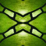 Approaching the stained glass in green colors, with symmetry and reflection effect, background and texture. Backdrop for color ads, creative pattern and stock illustration