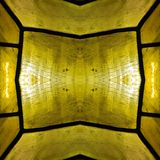 Approaching the stained glass in yellow colors, with symmetry and reflection effect, background and texture. Backdrop for color ads, creative pattern and royalty free stock photos
