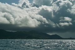 Approaching storm, below & above. Storm is above the tropical island with the rain on the right side.  Shadow of clouds is covering island and sea.  The upper Royalty Free Stock Photo