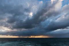 Approaching storm clouds. Approaching storm cloud with rain over the sea during sunrise Royalty Free Stock Photos