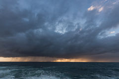 Approaching storm clouds. Approaching storm cloud with rain over the sea during sunrise Stock Photos