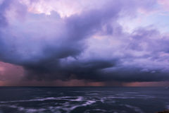 Approaching storm clouds. Approaching storm cloud with rain over the sea during sunrise Royalty Free Stock Photography