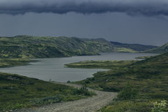 Approaching storm front in the highlands. A view of the green hills and the lake. Arctic summer, the tundra, Norway Royalty Free Stock Image