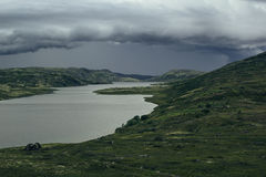 Approaching storm front in the highlands. A view of the green hills and the lake. Arctic summer, the tundra, Norway Stock Photo