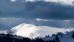 Some dark storm clouds are approaching the peak of a mountain covered in snow on a cold winter day Stock Image