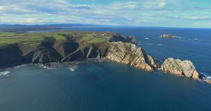 Approaching to cliffs in aerial view of the coast with fields on the top. And surrounded by sea in the north of Spain stock footage