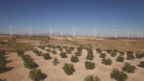 Approaching to wind turbines over tree field, 4k stock video footage