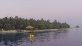 Approaching tropical island by boat at dusk. Approaching tropical island in the Maldives by boat at dusk stock footage