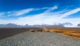 Approaching the Vatnajökull National Park. Vatnajökull National Park curious lonely rocks closing a gravel road Stock Photo
