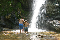 Approaching the waterfall. Two boys approaching a waterfall Stock Photo