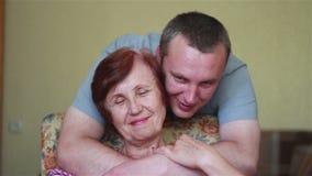 Approcci del figlio e delicatamente abbracciare madre anziana video d archivio