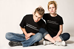 Appropriate - Inappropriate. Couple of teenagers in the studio on a white background royalty free stock image