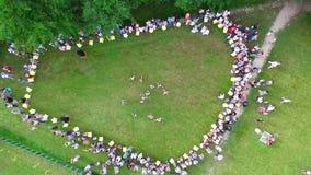 Approssimazione aerea nell'anello della gente che guarda una prestazione di ballo sulla natura qui sopra archivi video