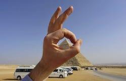 Approuvez le signe La main du ` s d'hommes montre correct avec les pyramides de Gizeh image libre de droits