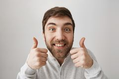 Approval and positive reaction concept. Studio shot of funny european guy smiling broadly, showing thumbs up and being. Excited of hearing great idea, standing Royalty Free Stock Photos