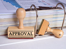 Approval stamp. Wooden rubber stamp marked approval next to binder with spreadsheets and graphs Stock Photos