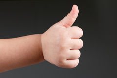 Approval thumbs up like sign, child hand gesture  over dark background Stock Photography