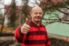 Approval of work, thumb up. The man in the village Royalty Free Stock Image