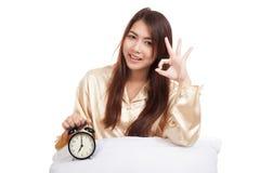 APPROVAZIONE asiatica felice di manifestazione della ragazza con il cuscino e la sveglia Fotografia Stock