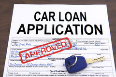 Approved car loan application form. And key on desktop stock photos