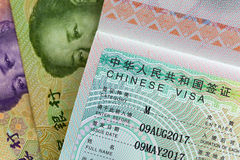 Approved China Business Visa M Visa on Chinese Yuan currency b. Closeup of approved China Business Visa M Visa on Chinese Yuan currency banknotes money Royalty Free Stock Image