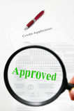 Approved credit. A credit application and magnifying glass with Approved text stock images