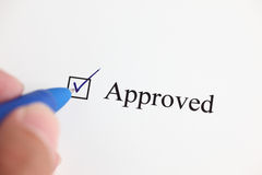 Approved. Hand with ballpoint pen marking the Approved checkbox on a document. Close-up Stock Images