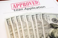 Approved Loan app. Lication form and assorted cash royalty free stock photo