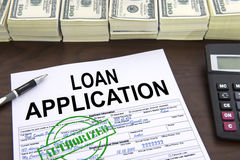 Approved loan application form and dollar bills. Approved loan application form and stacks of 100 dollar bills stock photography