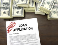 Approved loan application form and dollar bills. Approved loan application form and stacks of 100 dollar bills royalty free stock photo