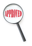 Approved. Magnifying glass focused on a stamp of approval royalty free stock photo