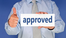 Approved - Manager with sign and thumb up. On blue background royalty free stock images