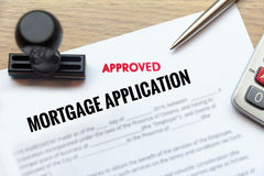 Approved mortgage application form lay down on wooden desk with. Rubber stamp and calculator stock photo