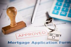 An approved Mortgage loan application form with house key and rubber stamp. Close up stock photo