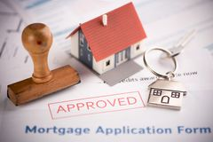 An approved Mortgage loan application form with house key and rubber stamp. Close up stock images