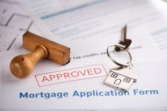 An approved Mortgage loan application form with house key and rubber stamp. Close up stock photography