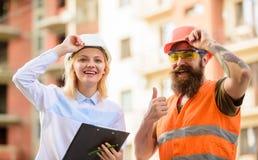 Approvisionnement établi par agent de maîtrise en matériaux de construction L'expert et le constructeur communiquent au sujet des photo libre de droits