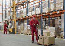 approvisionnement à chaînes - deux ouvriers dans l'entrepôt Images libres de droits