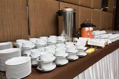 Approvisionnement - les rangées des tasses ont servi à la table de thé Photographie stock
