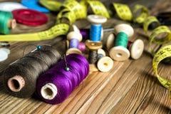 Approvisionnements de couture, bobines de fil, boutons, ciseaux, mesurant Photographie stock