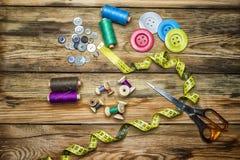 Approvisionnements de couture, bobines de fil, boutons, ciseaux, mesurant Photo libre de droits