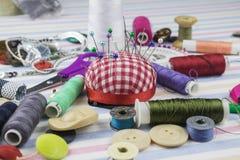 Approvisionnements de couture dispersés sur la table image stock